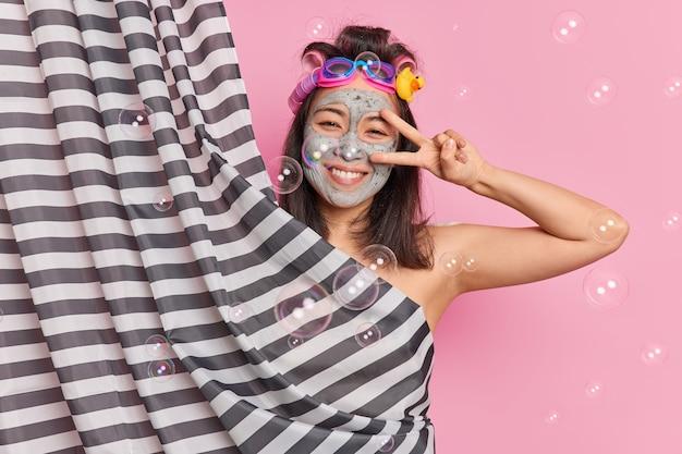 Позитивная беззаботная молодая женщина делает мирный жест сквозь улыбки глаз, с удовольствием применяет глиняную маску, наслаждается душем, применяет бигуди для волос, изолированные на розовом фоне с падающими мыльными пузырями