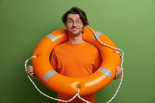 Positive caucasian adult man poses with safety equipment for smimming, smiles and eager to have summer holidays,