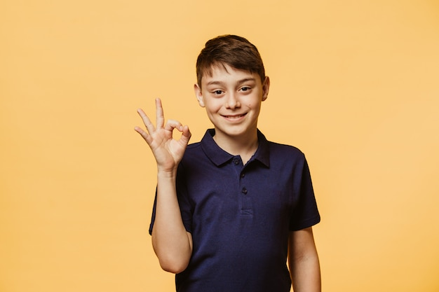Positive caucasian boy shows ok sign, demonstrates that everything is fine, agrees with people who surrounds him. confident cheerful boy gestures indoors. body language and human emotions concept