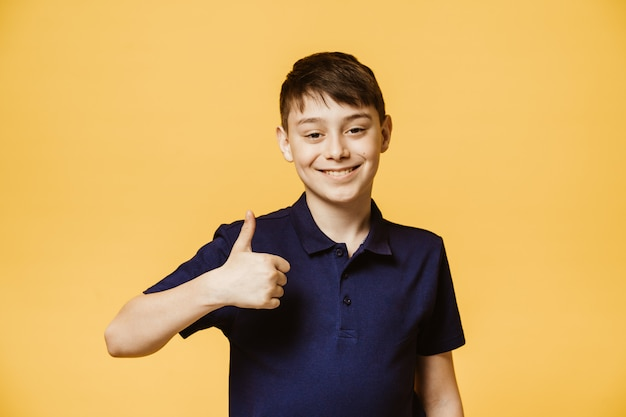 Positive caucasian boy shows thumb up sign, demonstrates that everything is fine. confident cheerful boy gestures indoors. body language and human emotions concept