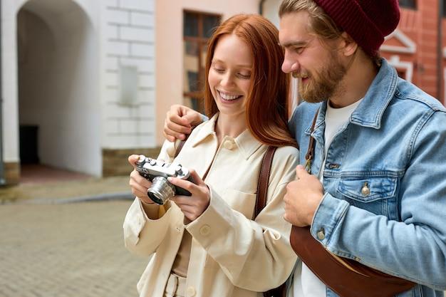 Позитивная кавказская пара туристов в повседневной одежде, стоя на улице с фотоаппаратом во время вакуума ...