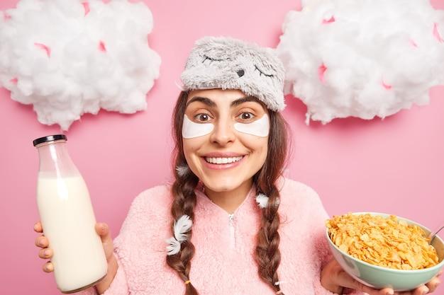 La ragazza caucasica positiva sorride dolcemente ha due trecce e piume bloccate in loro per fare colazione