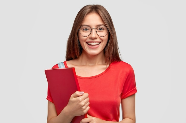 매력적인 미소를 지닌 긍정적 인 백인 소녀는 빨간 티셔츠를 입고 교과서를 들고 흰 벽에 모델을 들고 공부할 분위기가 있으며 좋은 시력을 위해 광학 안경을 착용합니다. 청소년, 학습 개념