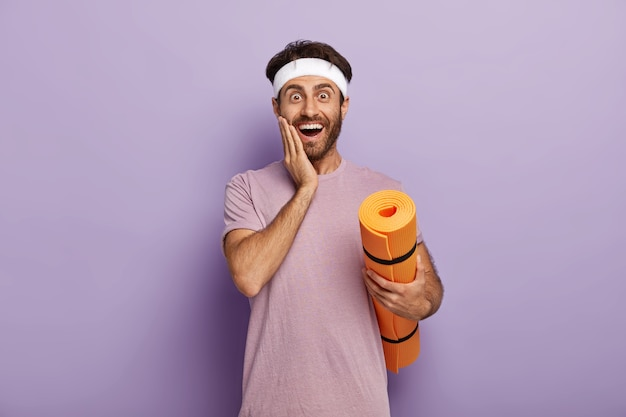 긍정적 인 백인 남자는 롤업 매트로 서 있고, 뺨을 만지고, 머리띠와 티셔츠를 입고, 보라색 벽에 서서 정기적으로 피트니스 운동을하고, 코치를 기다립니다.