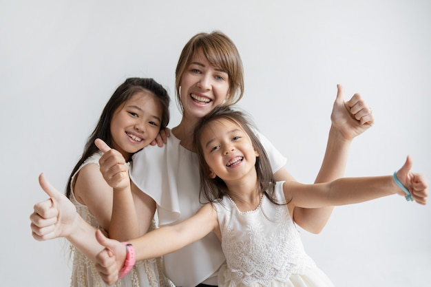 Positive caucasian mother and daughters showing thumbs up