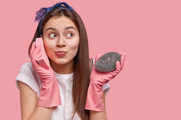 La donna caucasica positiva finge di parlare al telefono cellulare, tiene la spugna vicino all'orecchio, vestita in abiti casual