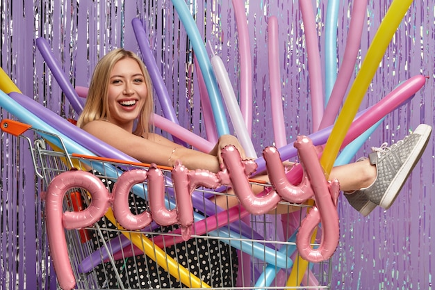 Positive caucasian woman with light hair, poses in shopping cart with colorful modeling balloons, being in good mood, celebrates anniversary, isolated over purple wall
