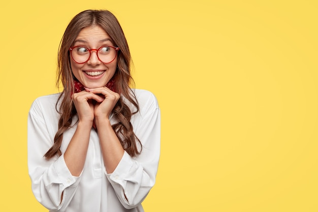 Positive caucasian woman with tender smile, keeps hands under chin, giggles positively aside, dressed in white shirt, stands against yellow wall with free space for your promotional content
