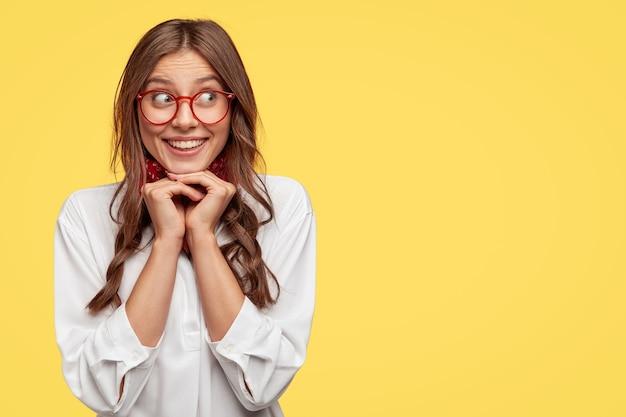 Positiva donna caucasica con tenero sorriso, tiene le mani sotto il mento, ridacchia positivamente da parte, vestita con una camicia bianca, si erge contro il muro giallo con spazio libero per i tuoi contenuti promozionali