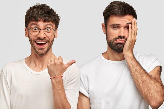 Giovane maschio caucasico positivo con capelli scuri, punta con il pollice al suo compagno scontento che si pente di qualcosa, tiene la mano sulla guancia, esprime emozioni diverse, isolato sopra il muro bianco