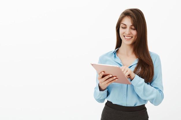 Positiva donna di affari affascinante bruna posa in studio