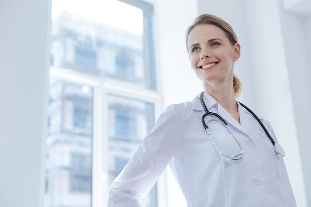 새로운 환자를 기다리며 행복을 표현하며 클리닉에 서있는 긍정적 인 매력적인 자격을 갖춘 개업의