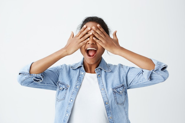 Positive cheerful afro-american female dressed casually holding her hands on closed eyes with open in excitement mouth expecting for surprise or gift. people, good news, positive emotions.