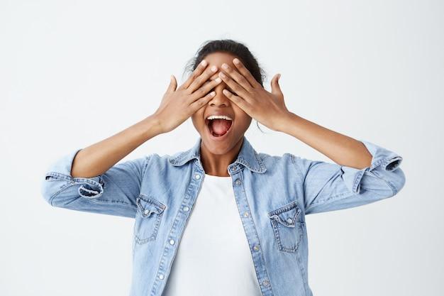 긍정적 인 쾌활한 아프리카 계 미국 흑인 여성 부담없이 놀라게하거나 선물을 기대하는 흥분 입에서 열린 눈을 감고 그녀의 손을 잡고 입고. 사람, 좋은 소식, 긍정적 인 감정.