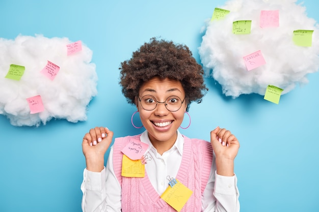 긍정적 인 쾌활한 아프리카 계 미국인 여성은 필기 작업이있는 스티커 메모로 둘러싸인 둥근 안경 형식의 옷을 입는 것에 대한 칭찬을 듣고 기뻐서 앞에서 손을 들었습니다.