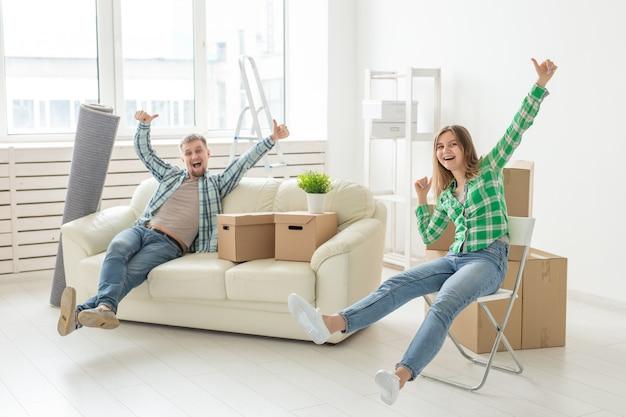 Позитивная веселая пара радуется переезду своей новой квартиры, сидя в гостиной