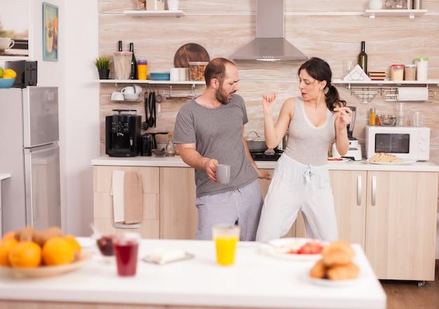 -パジャマを着てキッチンで朝食をとりながら踊るポジティブで陽気なクレイジーカップル。のんきな妻と夫が笑って楽しんで面白い人生を楽しんでいる本物の既婚者ポジティブ幸せな再