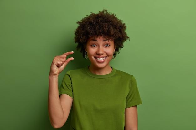 긍정적 인 쾌활한 짙은 피부의 곱슬 머리 여자는 손가락으로 아주 작은 것을 만들고, 작은 가격이나 급여를 줄이며, 큰 물건이 아닌 몸짓을 보여주고, 이빨로 웃으며, 녹색이 우세합니다.