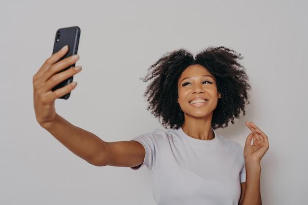 現代のスマートフォンのカメラで写真を撮るポジティブで陽気な暗い肌の女性、携帯電話で自分撮りをしているカジュアルな白いtシャツを着た陽気なアフリカの女性、幸せそうに笑う