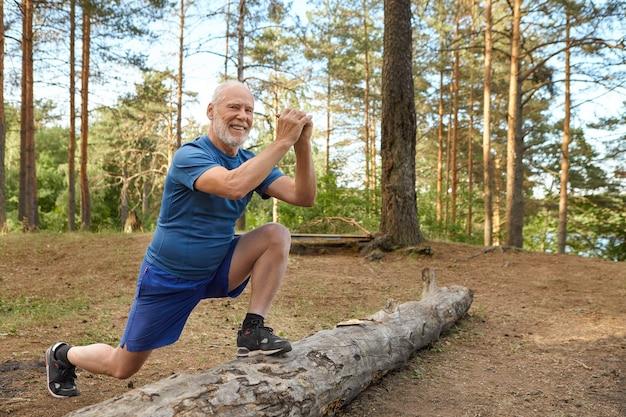 Pensionato maschio europeo allegro positivo in t-shirt, pantaloncini e scarpe da ginnastica con routine di riscaldamento all'aperto, in piedi sul tronco con un piede, tenendosi per mano davanti a lui, facendo affondi, sorridente