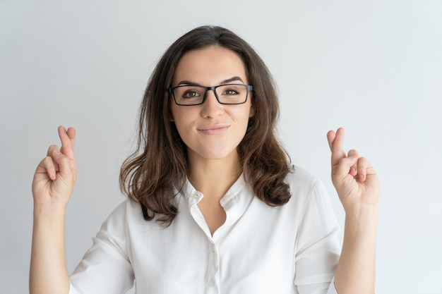 Positive cheerful female student in glasses making wish.
