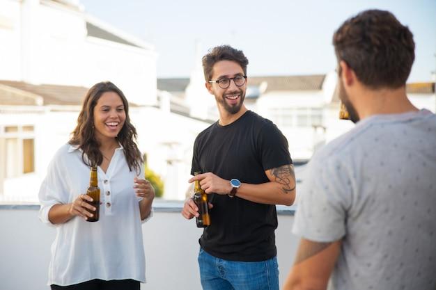 Позитивные веселые друзья разговаривают, смеются и пьют пиво