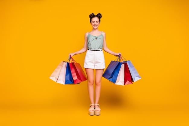 Позитивная жизнерадостная девушка увлекается покупками покупает много покупок держит сумки