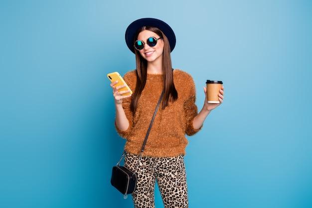 Позитивная веселая девушка пугает использование смартфона следить за репостом читать блоггеры держат кружку с кофеином, напитком, коричневые брюки, ретро винтажная шляпа, изолированная стена синего цвета