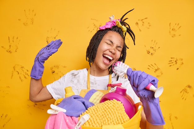 ポジティブで陽気な主婦が、マイクが汚れた服を着ているかのようにブラシを持って歌を歌う洗濯かごの近くに立ってゴム手袋を着用して黄色い壁の周りを馬鹿にする