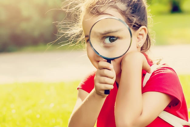 Positive cheerful little girl looking through a magnifying glass outdoors