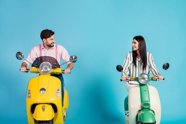 긍정적 인 쾌활한 사랑스러운 아내 남편 자전거 타는 사람 드라이브 헬기 모터 자전거 길 여행 착용 스트라이프 핑크 formalwear 셔츠 파란색 벽 위에 절연