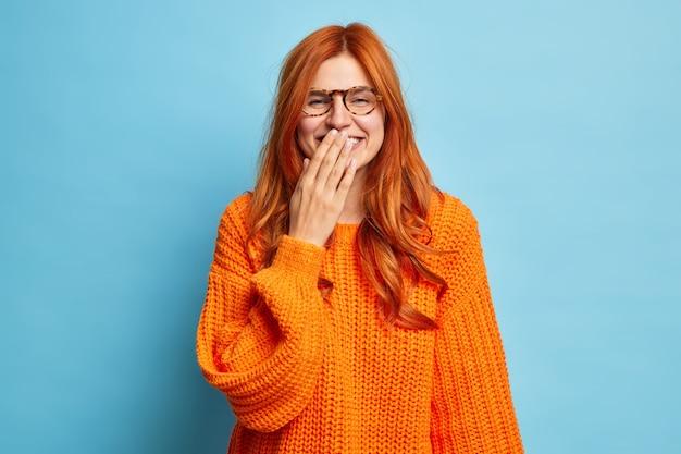 Позитивная жизнерадостная рыжая женщина счастливо улыбается, пытается скрыть эмоции, прикрывает рот рукой, стесняется, слышит веселую шутку, носит вязаный свитер.