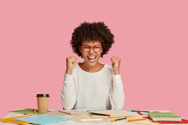 Ragazza studentessa allegra positiva in posa alla scrivania contro il muro rosa