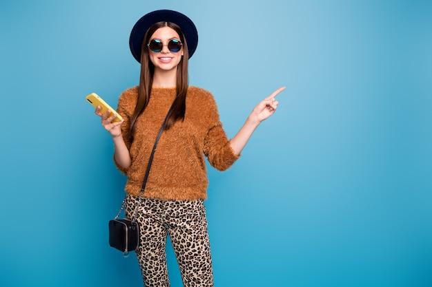 Позитивная жизнерадостная студентка использует смартфон, репост рекламы, продвижение, указательный палец, одежда copyspace, ретро шляпа, сумочка, коричневый свитер, повседневные брюки, изолированные на стене синего цвета