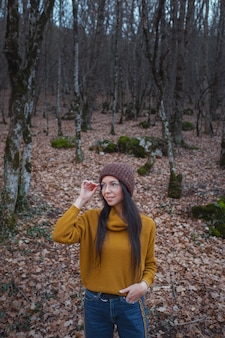 Positive cheerful woman enjoy autumn in park or woods wear yellow pullover and hat, glasses. mood happy hipster girl in late autumn forest road trip