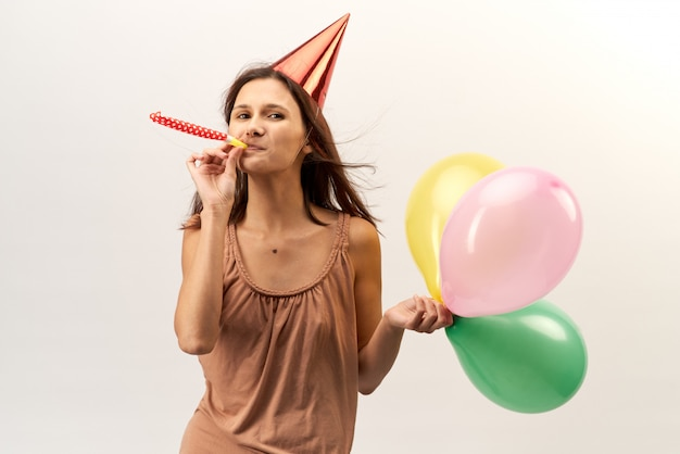 Positive cheerful young girl in a party hat and with trumpet and baloons poses for a portrait with flowing long hair. studio portrait on isolated white background. holiday, birthday, achievement.