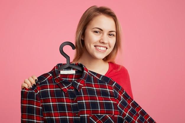 肯定的な陽気な若い女性がハンガーにファッショナブルな市松模様のシャツを宣伝します