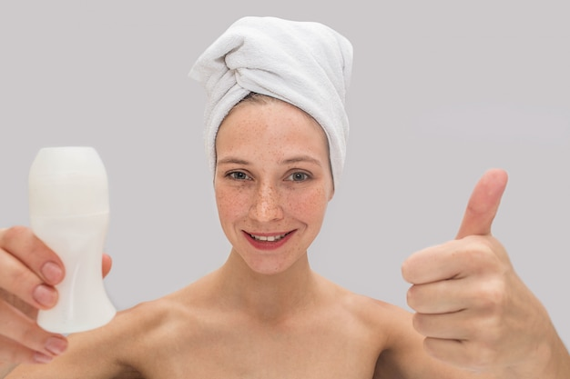 Positive and cheerful young woman stands and looks. she holds her big thumb up and deodorant in another hand. there are white towel around her hair.
