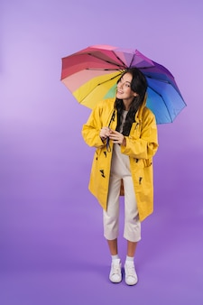 Positive cheery cute brunette woman in yellow raincoat posing isolated over purple wall wall holding umbrella.