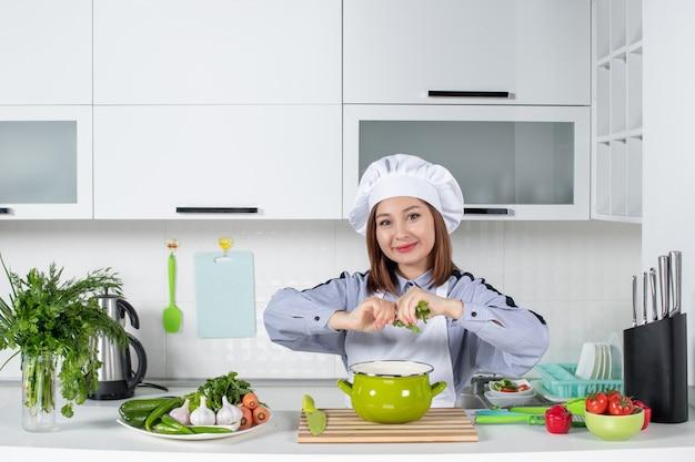 ポジティブなシェフと新鮮な野菜、調理器具、白いキッチンの鍋にグリーンを追加