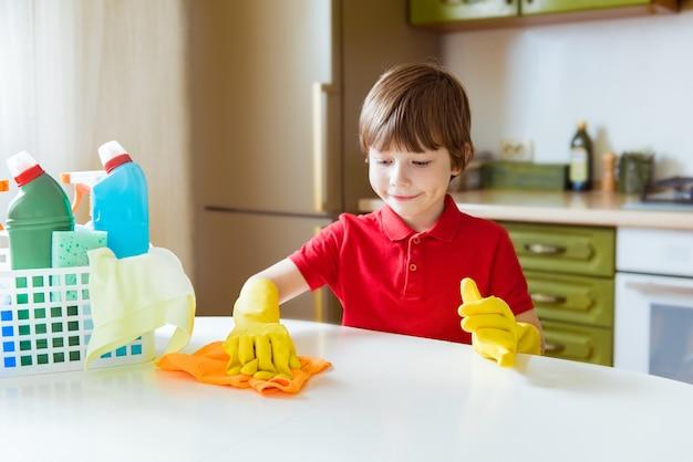 ポジティブな男の子は台所のテーブルを掃除します。笑顔の子供はほこりをこすります。家、ハウスキーピングの概念