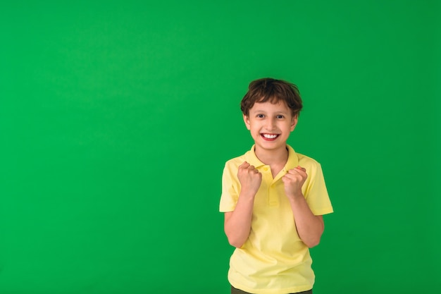 Positive child exults with clenched fists, celebrates victory