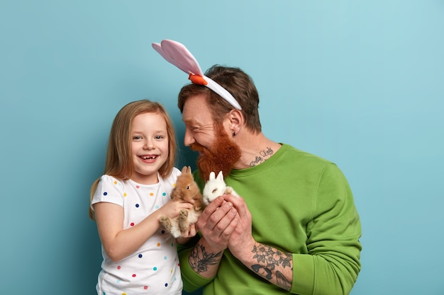 Positive child and father play with two fluffy rabbits