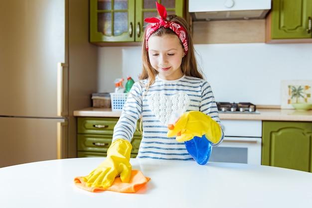 ポジティブな子の女の子が台所のテーブルを掃除します。ティーンエイジャーはほこりをこすります。ぼろきれとスプレーボトルの洗剤で掃除するゴム製の保護黄色の手袋を着用して笑顔の子供。家、ハウスキーピングの概念