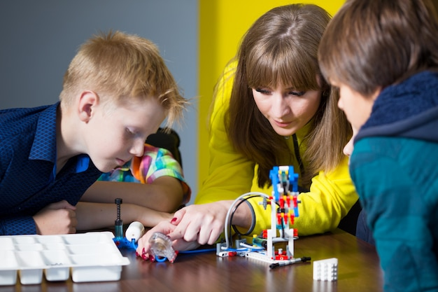 Positive children play and assemble the constructor in the children's room.