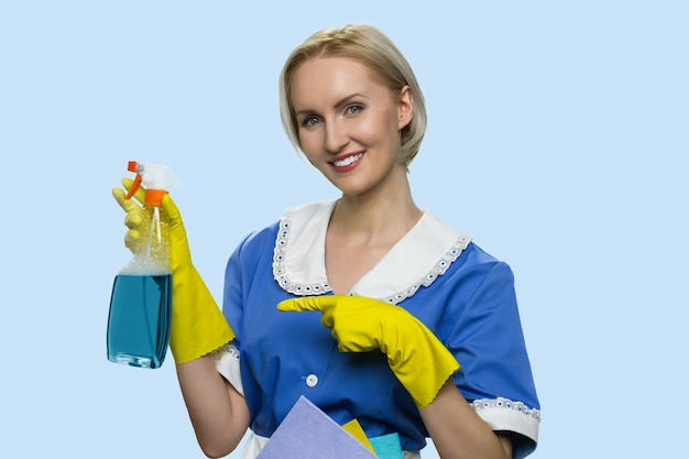 Positive cleaning lady is pointing at cleaning spray