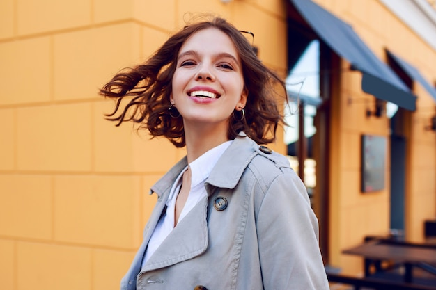 Positive close up portrait of smiling happy short haired girl with perfect white teeth having fun. windy hairs. autumn mood .