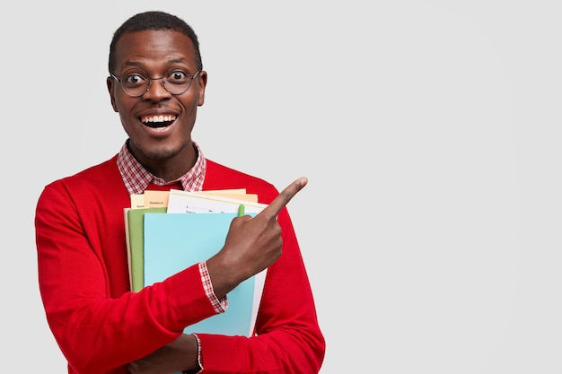 Positive college student has dark skin, carries folders and book, points with cheerful expression aside, has toothy smile