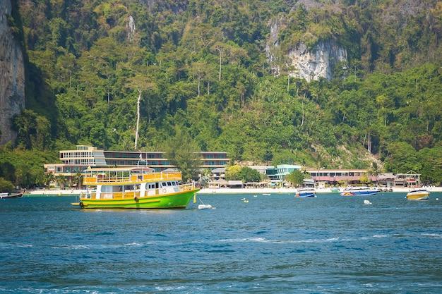 라일레이 해변 근처에서 순항하는 녹색 및 노란색 승객 관광 쾌속정에 긍정적인 색상