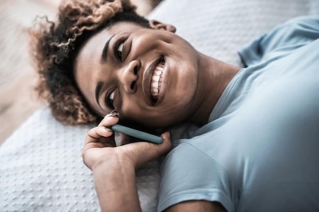 ポジティブなコミュニケーション。横を向いて耳の近くにスマートフォンで横たわっている暗い肌のきれいな女性の幸せな笑顔のクローズアップ